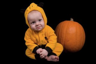 Baby dressed in a costume next to a Halloween pumpkin.