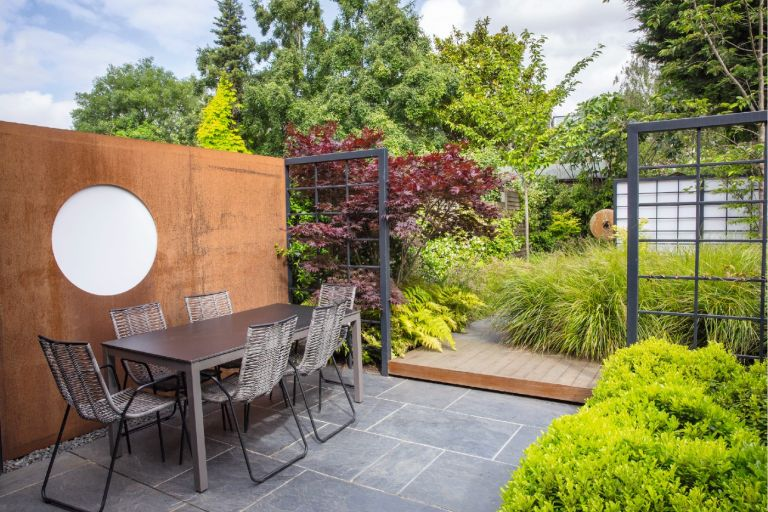 Black square trellis frames an outdoor seating area on a patio