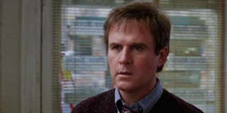 Charles Grodin standing with a slightly confused face in Dave.