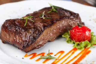 A steak sits on a dinner plate