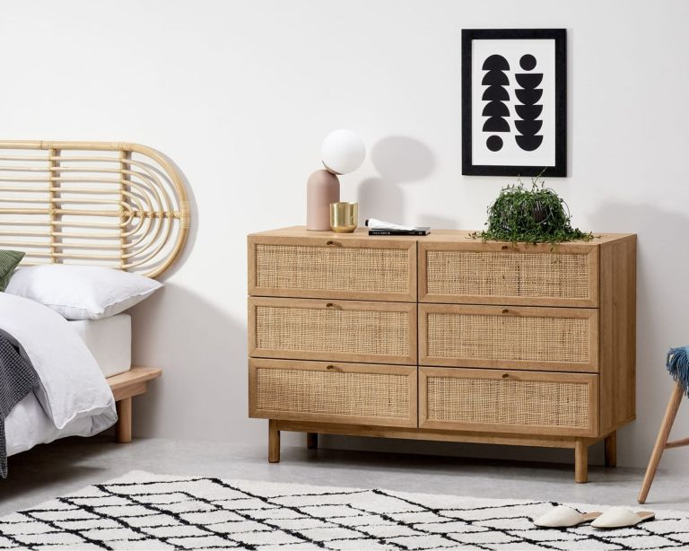 Pavia Wide Chest of Drawers in bedroom beside bed with pink lamp and plant on top