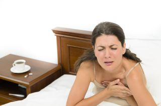 woman having a heart attack in bed