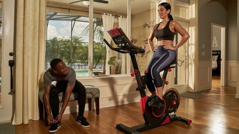 Echelon Smart Connect EX3 Max Exercise Bike review: a woman works out on the bike whilst a muscular man watches on
