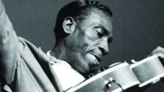 A black and white picture of T-Bone walker playing the guitar