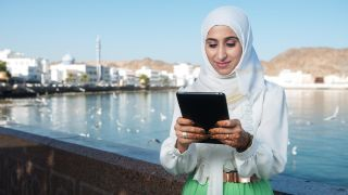 Woman in Oman looking at a tablet.