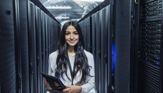 Mixed race technician holding digital tablet in server room - stock photo