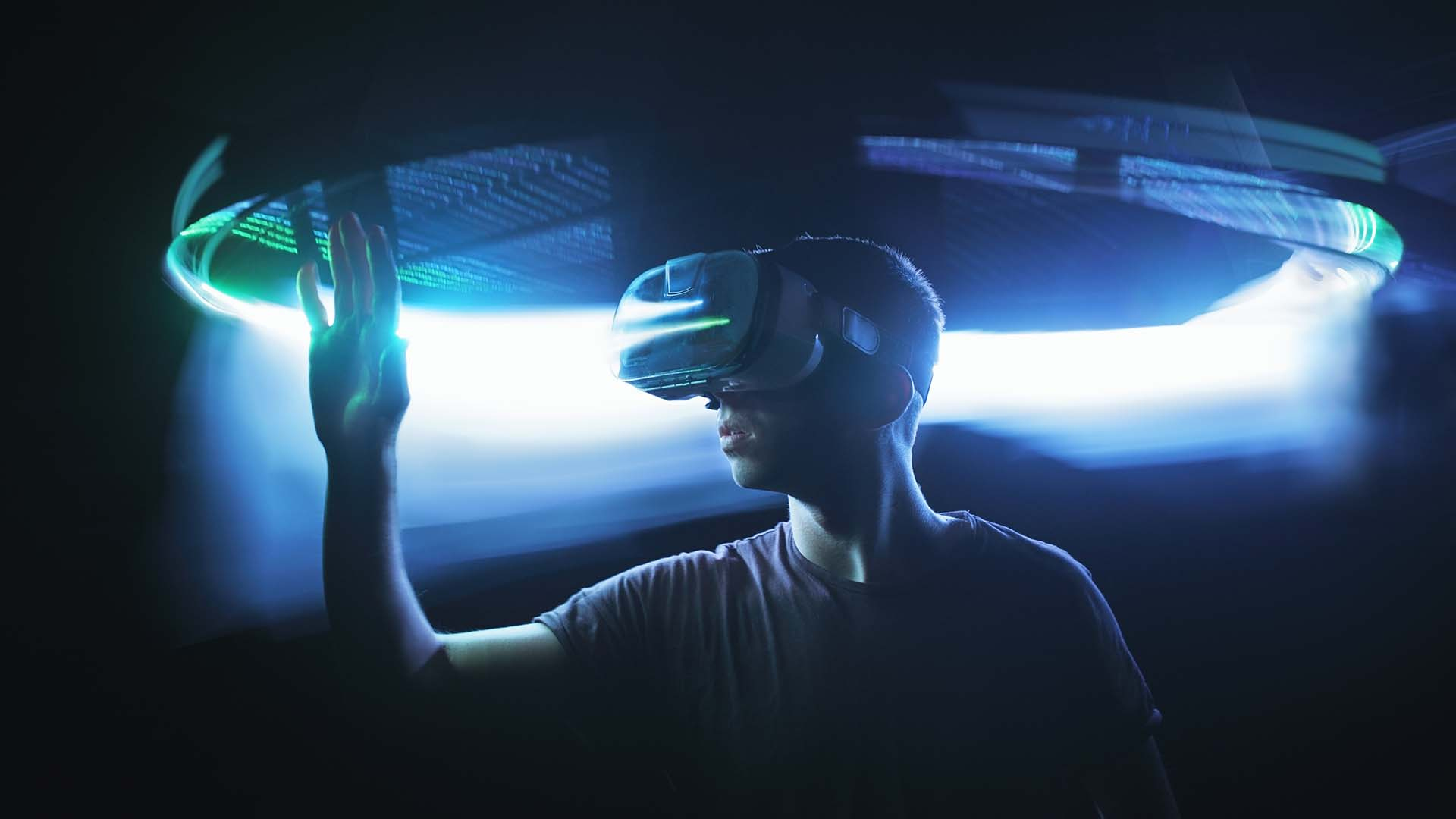 Man in Virtual Reality headset with hand extended out in front of him