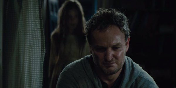 Pet Sematary Jason Clarke looking concerned in the basement, with his zombie daughter behind him