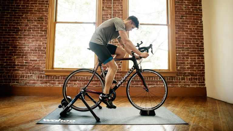 The best turbo trainer can help you get road fit, just like how the person on this picture, riding a turbo indoors in front of large windows