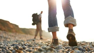 A close up of two people hiking on a pebble beach wearing jeans