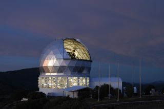 The mirror of the 9.2-meter Hobby-Eberly Telescope is visible through the open louvers in this twilight view. In daylight, the flagpoles on the right show the flags of the five HET partner institutions.