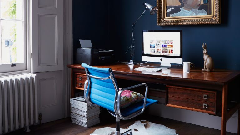 Dark blue home office with dark wooden desk and bright blue office chair