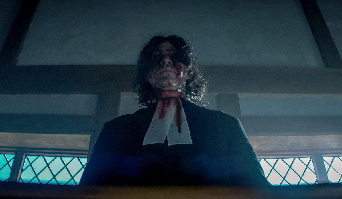 Michael Chandler stands at the pulpit with a bloody face in Fear Street: Part 3 - 1666.