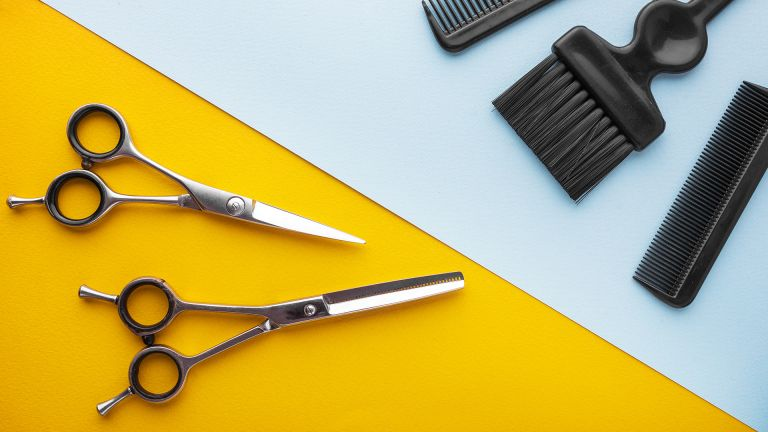 hairdressing scissors and tools on blue and yellow backdrop