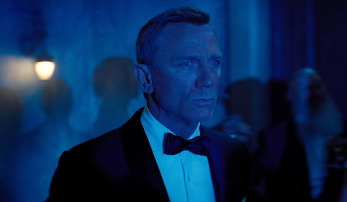 No Time To Die James Bond looks worried in a blue lit setting