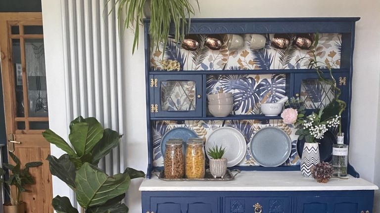 Kitchen dresser painted blue with floral wallpaper backing