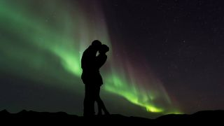 A couple silhouetted in front of the northern lights