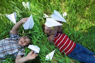 Two boys play with paper airplanes.