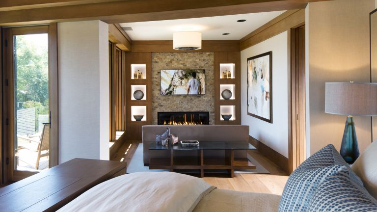 Bedroom TV ideas with a television nook featuring a contemporary fireplace and seating