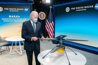 President Joe Biden examines a model of NASA's Mars helicopter Ingenuity, which on April 19 became the first aircraft to perform a powered, controlled flight on a world beyond Earth.