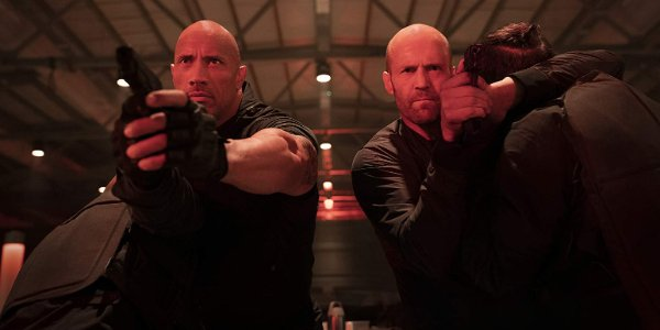 Hobbs & Shaw aiming their guns at a door, bathed in red light