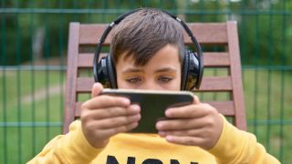 A child streams content on his phone while wearing headphones.