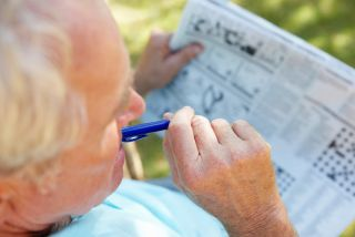 An older man works on a puzzle in his newspaper