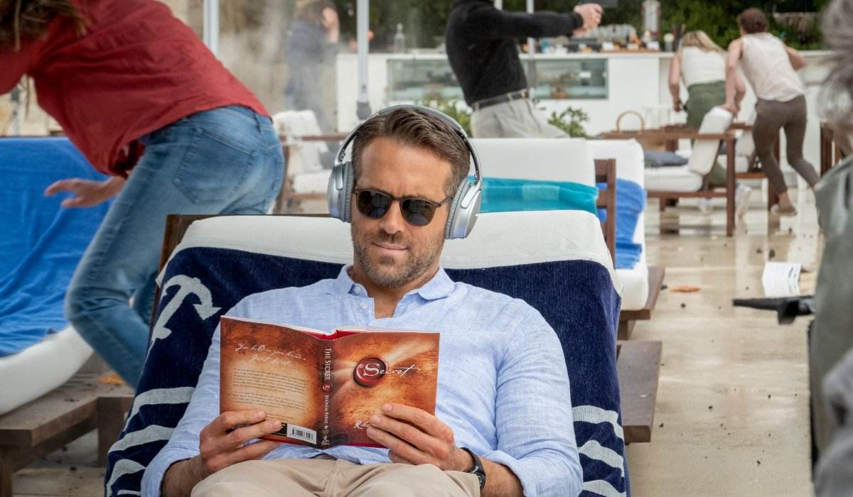 Ryan Reynolds tries to read The Secret in peace in The Hitman's Wife's Bodyguard.