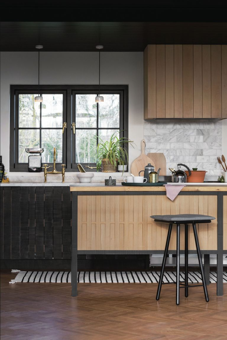 Slat wood kitchen island and high cabinet teamed with white marble effect wall tiles, dark accents and wooden herringbone flooring