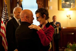 Captain Mark Kelly hugs his wife Congresswoman Gabrielle Giffords after receiving the Legion of Merit from Vice President Joe Biden during Captain Kelly's retirement ceremony in the Secretary of War Suite in the Eisenhower Executive Office Building, in Wa