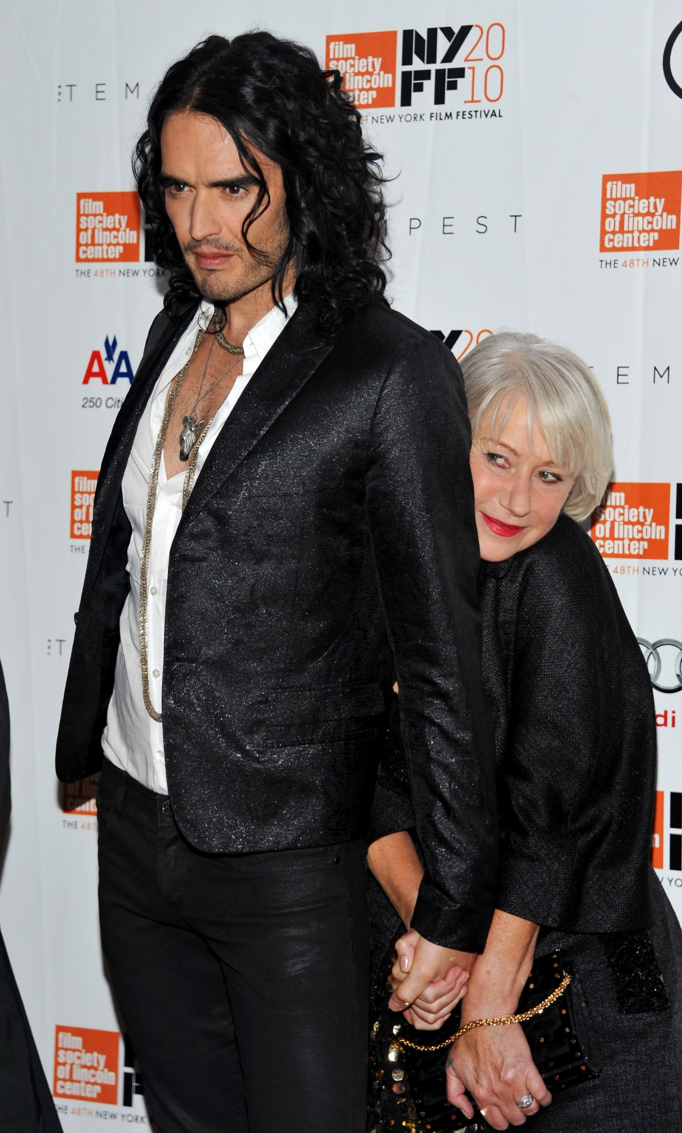 Helen Mirren hites behind her Tempest co-star Russell Brand on the red carpet