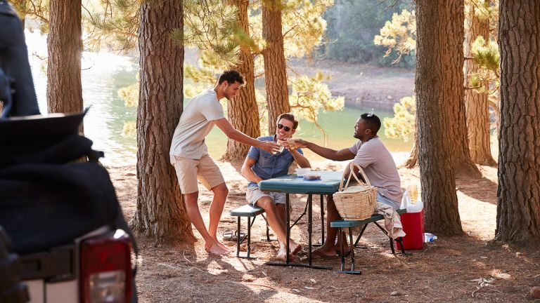 best camping tables: men eating outside