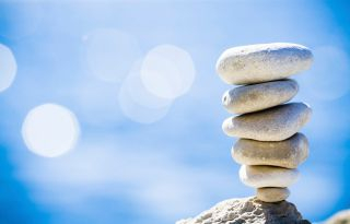 Tall stack of smooth stones in front of blue sky