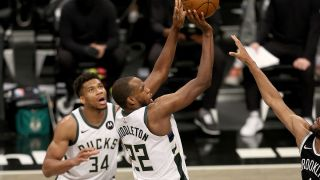 Khris Middleton #22 of the Milwaukee Bucks shoots the game winning basket as teammate Giannis Antetokounmpo looks on in the final minutes of overtime during game seven of the Eastern Conference second round at Barclays Center on June 19, 2021 in the Brooklyn borough of New York City.