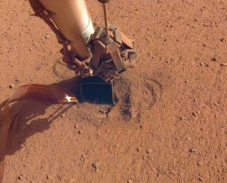 "NASA's InSight Mars lander has used the scoop on the end of its robotic arm to help the mission's burrowing heat probe, known as the ""mole,"" get and stay underground."