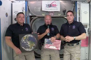 "NASA astronaut and SpaceX Crew Dragon spacecraft commander Doug Hurley, flanked by his crewmate Bob Behnken and Expedition 63 commander Chris Cassidy, displays the U.S. flag ""captured"" by SpaceX as the first U.S. company to launch astronauts to the space station, on Monday, June 1, 2020."