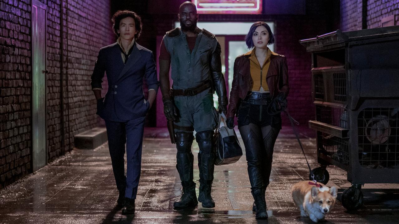 John Cho, Mustafa Shakir, and Daniella Pineda walking down an alley with Ein in Cowboy Bebop.