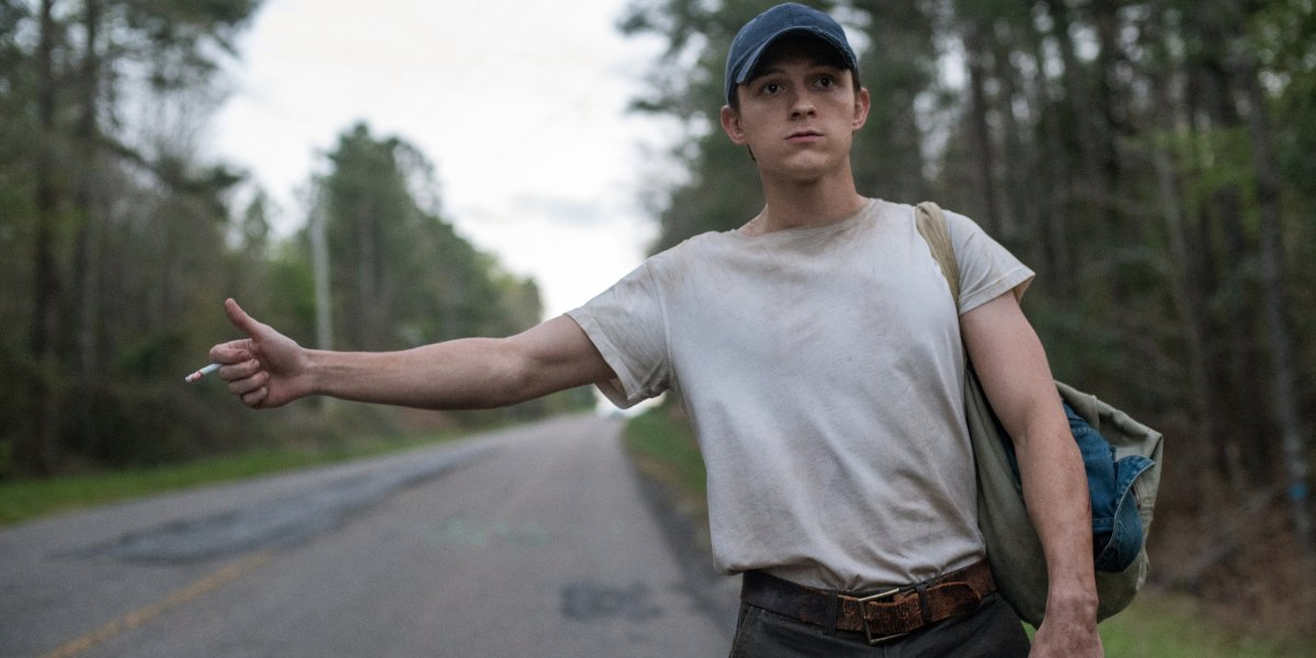 The Devil All The Time Tom Holland hitchhikes in the woods