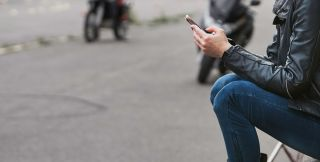 Woman sitting down and using smartphone in profile]