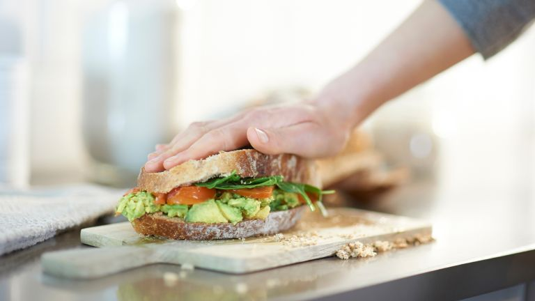 Woman making a vegan sandwich, with smashed avocado and tomato