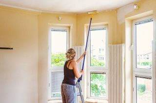 Decorator painting a ceiling with a roller