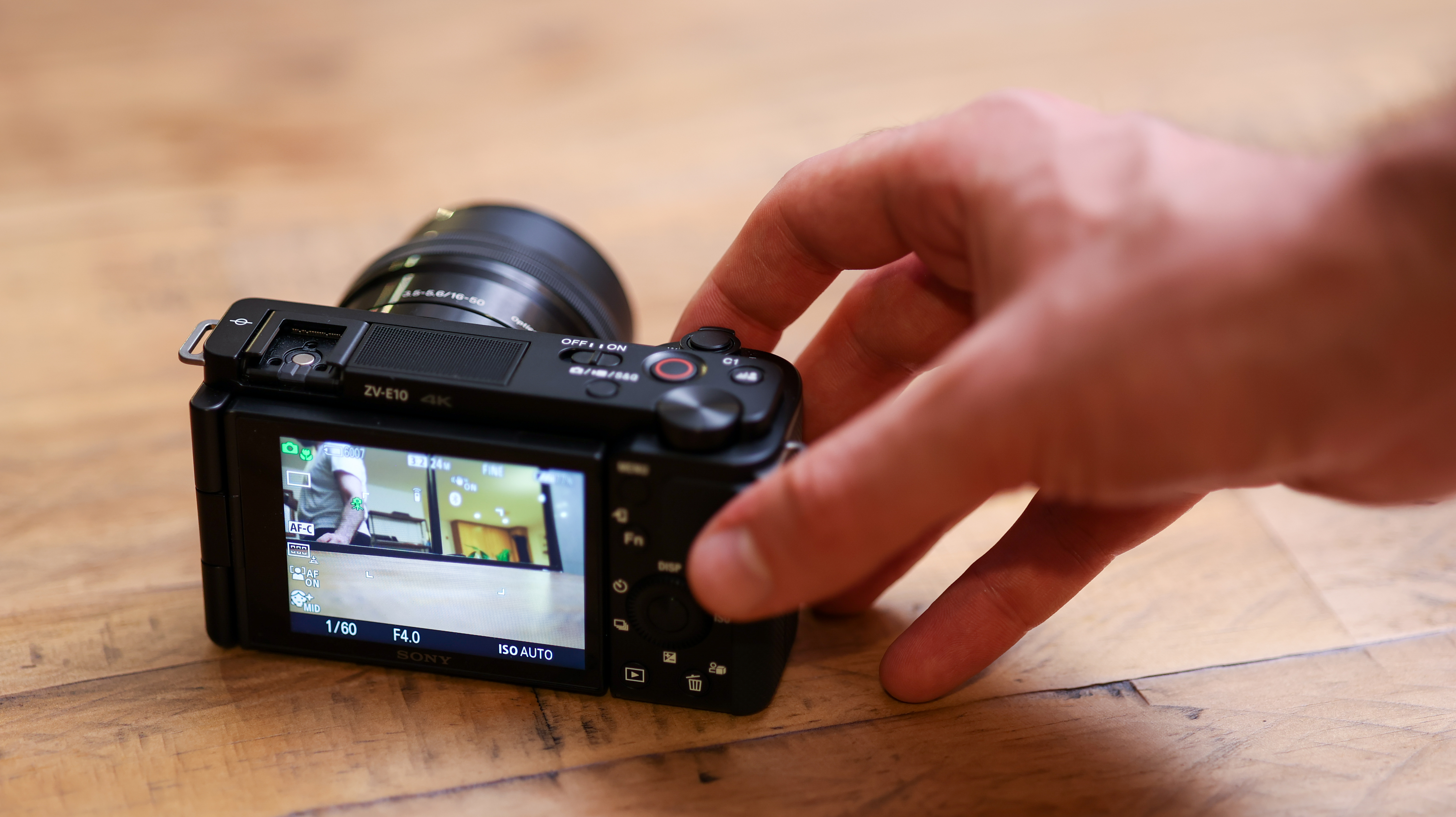 A hand operating the Sony ZV-E10 while it sits on a wooden table