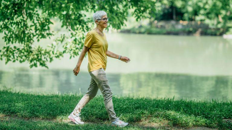 Middle-aged woman walks alongside a river
