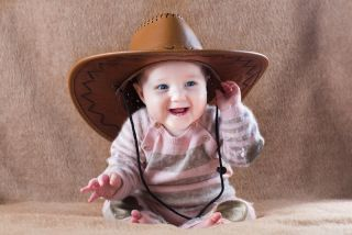 baby wearing a cowboy hat