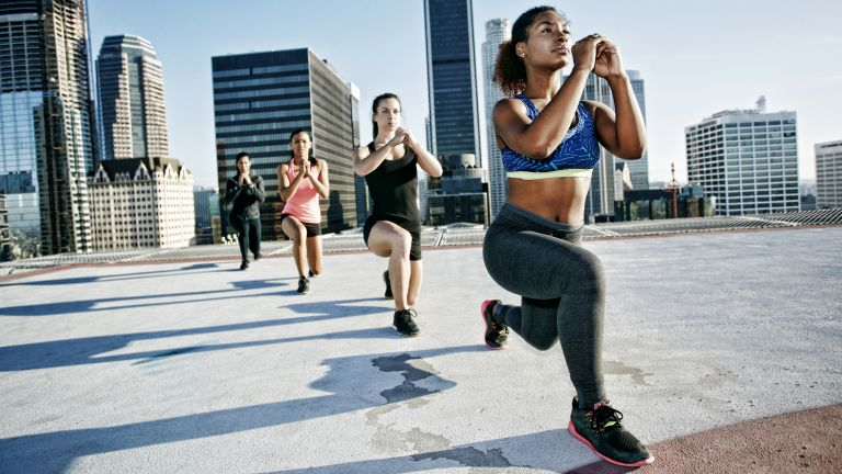Woman performing lunges on a rooftop