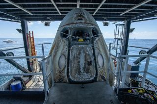"""The SpaceX Crew Dragon """"Endeavour,"""" which flew astronauts Bob Behnken and Doug Hurley to space, is positioned on the SpaceX GO Navigator recovery ship after splashing down in the Gulf of Mexico on Sunday, Aug. 2, 2020. The spacecraft is destined to fly again, but could land in the Smithsonian, someday."""