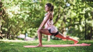 A woman does yoga outside surrounded by trees