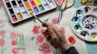 Watercolour techniques - A photo of a woman painting flowers with watercolours.