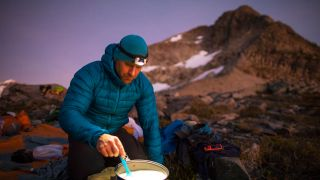 man cooking in the mountains in one of our best down jackets