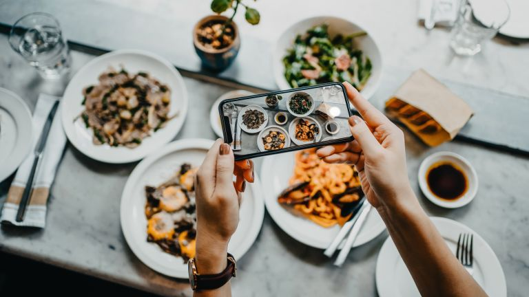 Woman taking a photo of healthy meals
